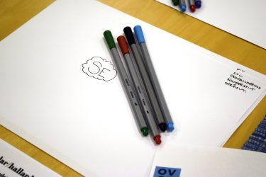Fyra pennor i olika färger ligger ovanpå ett papper.