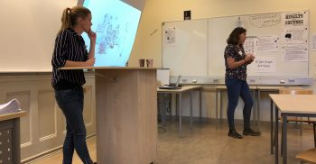 Kvinnor föreläser framför projicerad presentation.
