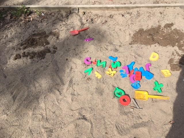 Plastbokstäver i sandlåda.