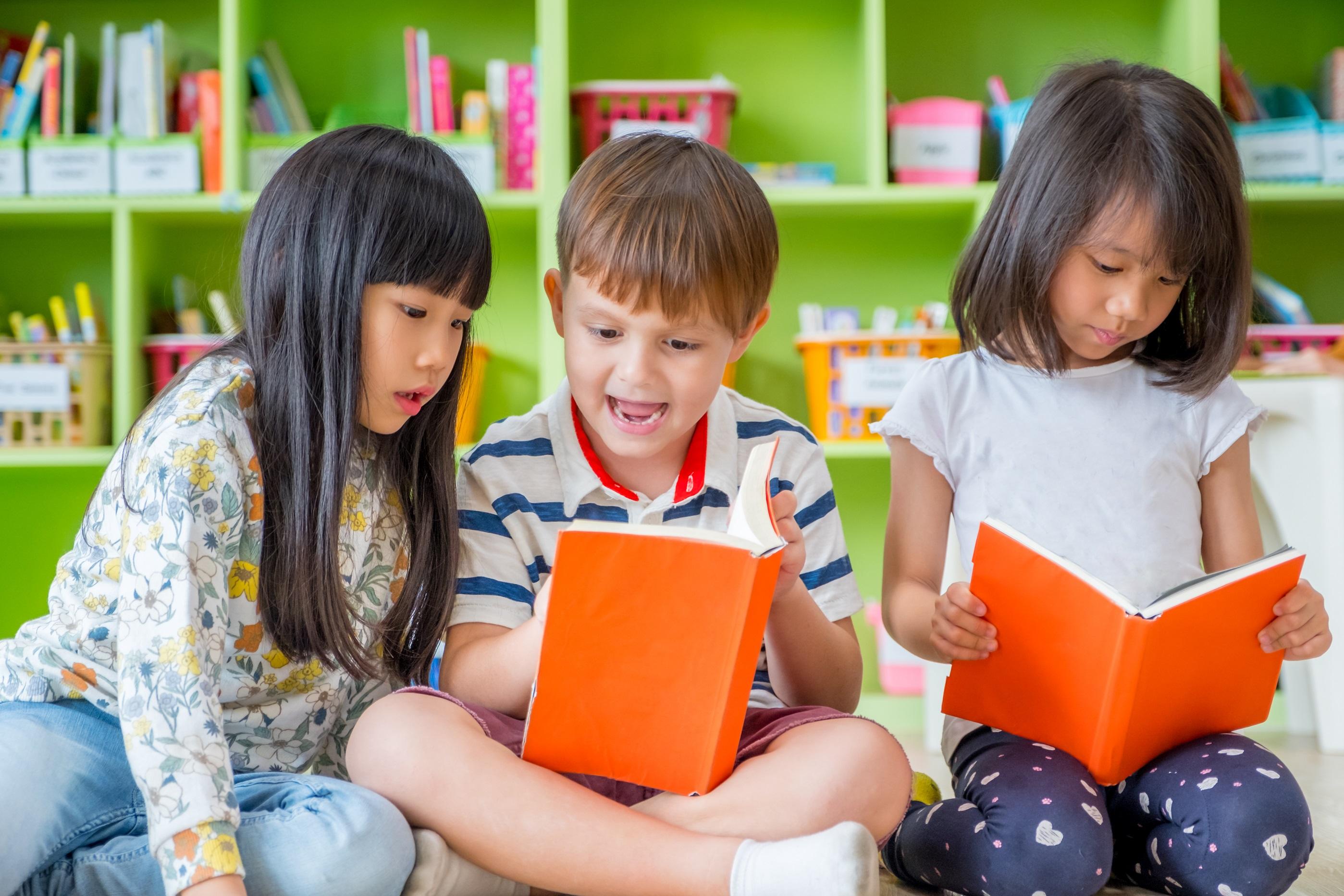 Barn sitter på golvet och läser i böcker.