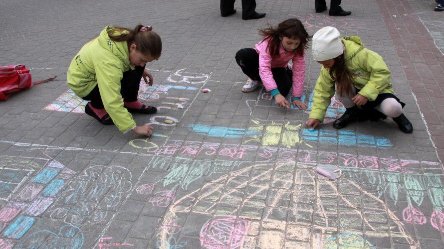 Barn ritar på gatan med kritor.