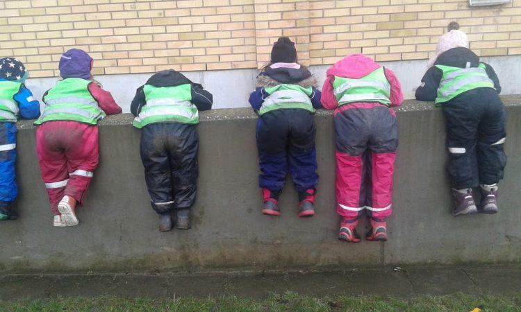 Barn hänger på stenmur.