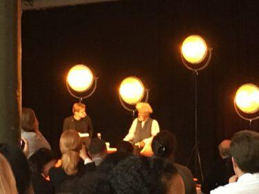 Två män samtalar på scen.