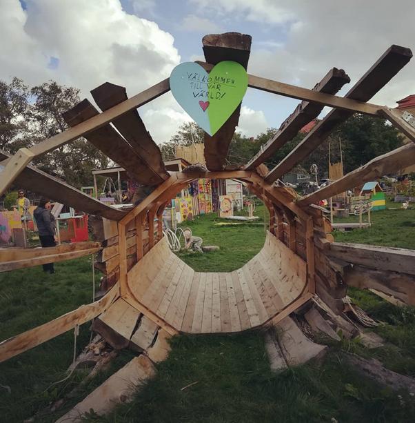 Träskulptur som välkomnar in på området.