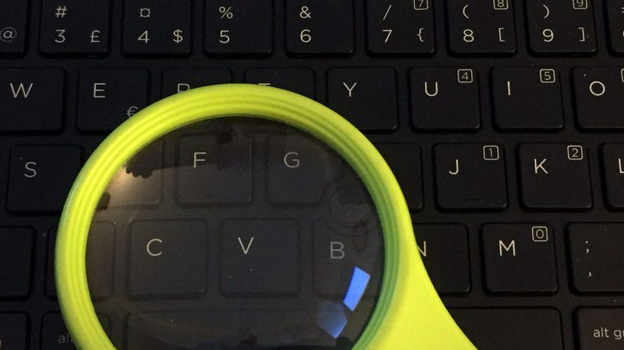 Förstoringsglas ligger på tangentbord.