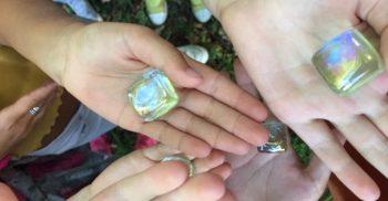 Barnhänder håller fram glasstenar.
