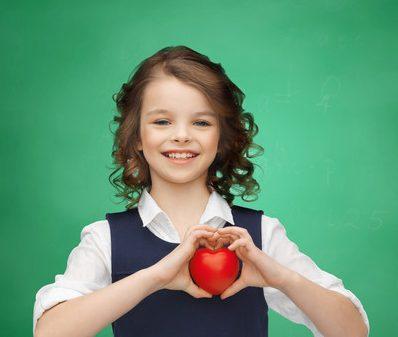Barn håller upp äpple och formar ett hjärta med händerna.