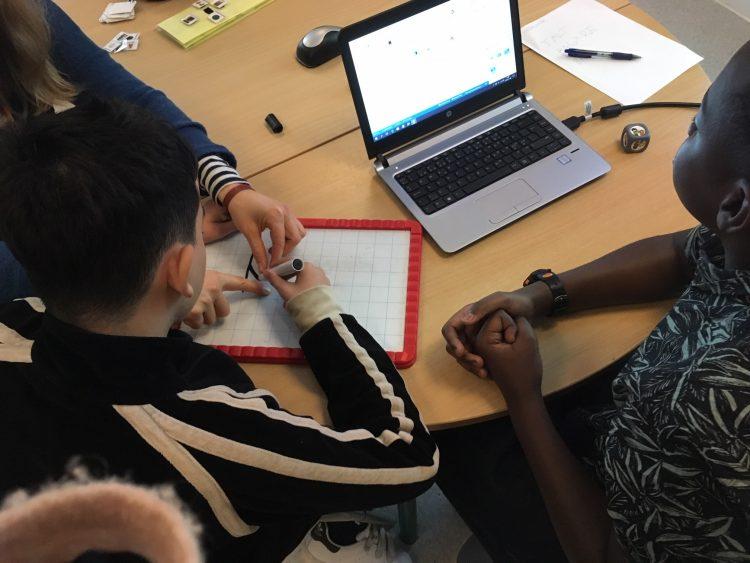 Elever jobbar vid bord med dator och tavla att skriva på.