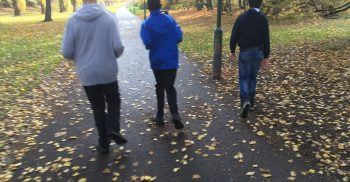 Tre barn springer längs med cykelbana.
