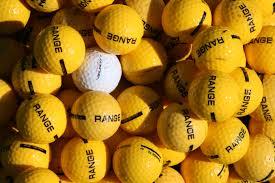 Vit golfboll i hav av gula golfbollar.