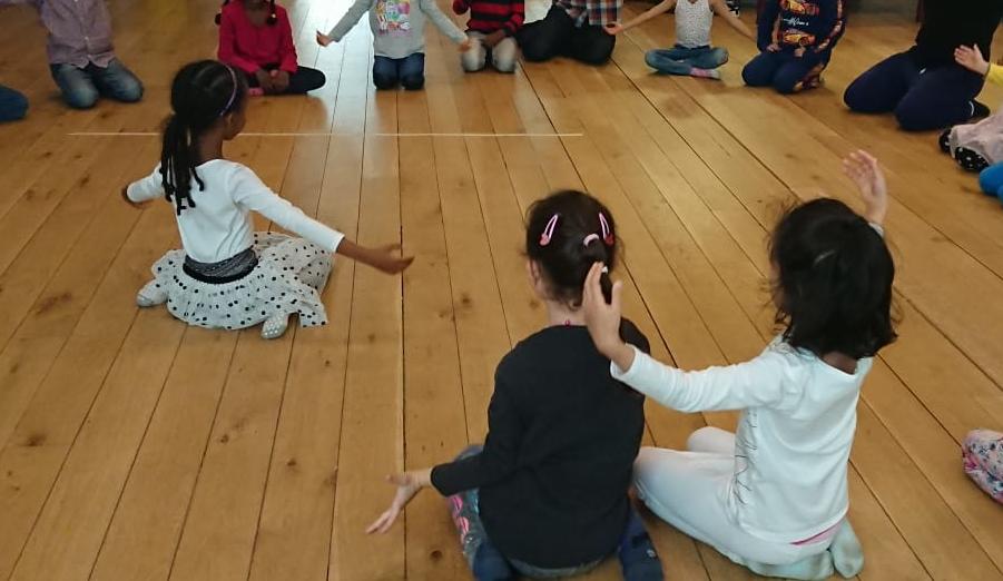 En liten flicka sitter på golvet och visar en rörelse, som kamraterna runt omkring härmar.