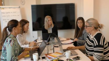Fem kvinnor sitter vid bord.