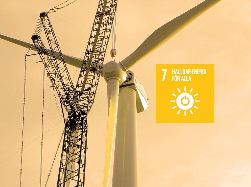 Vindkraftverk och skylt med globala målet nummer sju.