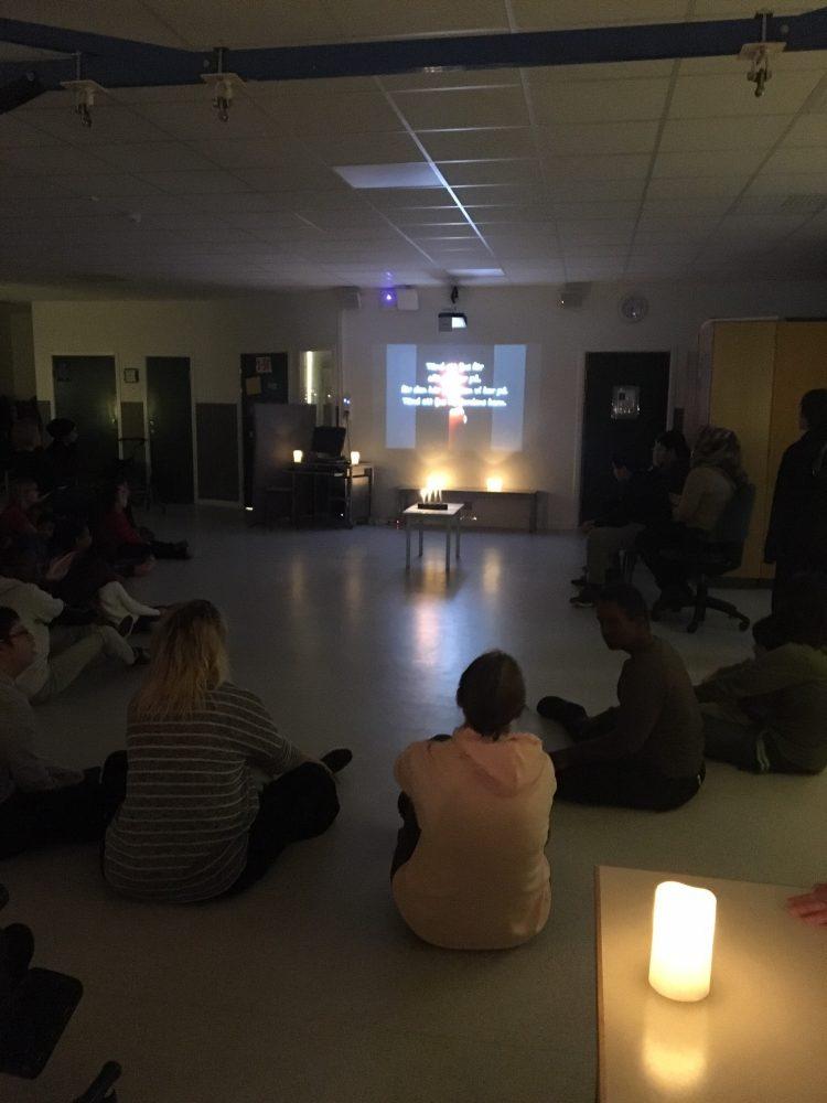 Människor sitter i ring på golvet med tända ljus.