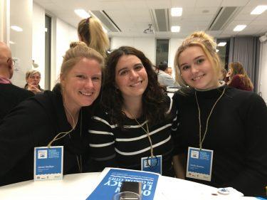 Tre kvinnor samtalar på konferens.