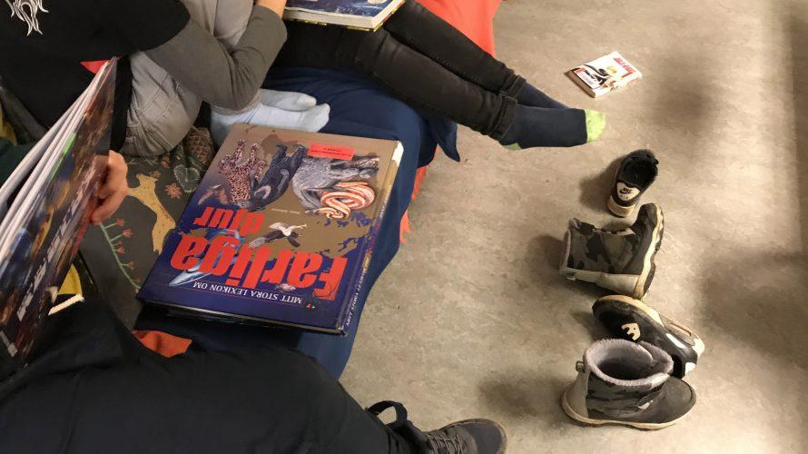 Barn sitter och läser i soffa och har tagit av skorna som ligger nedanför dem.