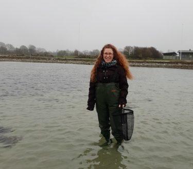 Katrina Fornell står i havet med vadarbyxor på.