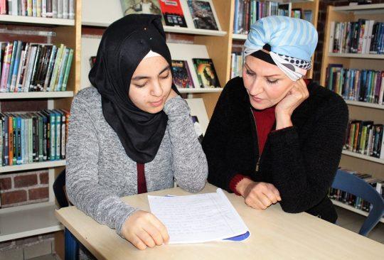 Två kvinnor sitter vid bord och läser i texthäfte.