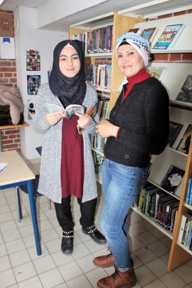 Noor och Hanaa står framför bokhylla.