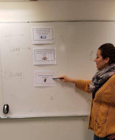 Kvinna står vid whiteboard där det finns laminerade lappar uppsatta.