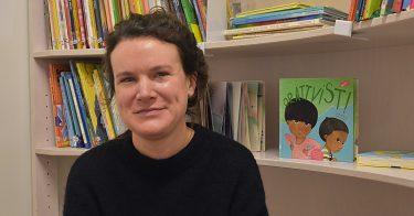 Kristina Ivert framför böcker i bokhylla