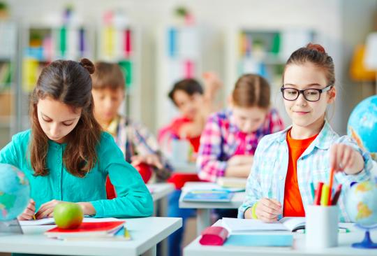 Två elever sitter och jobbar i skolbänk.