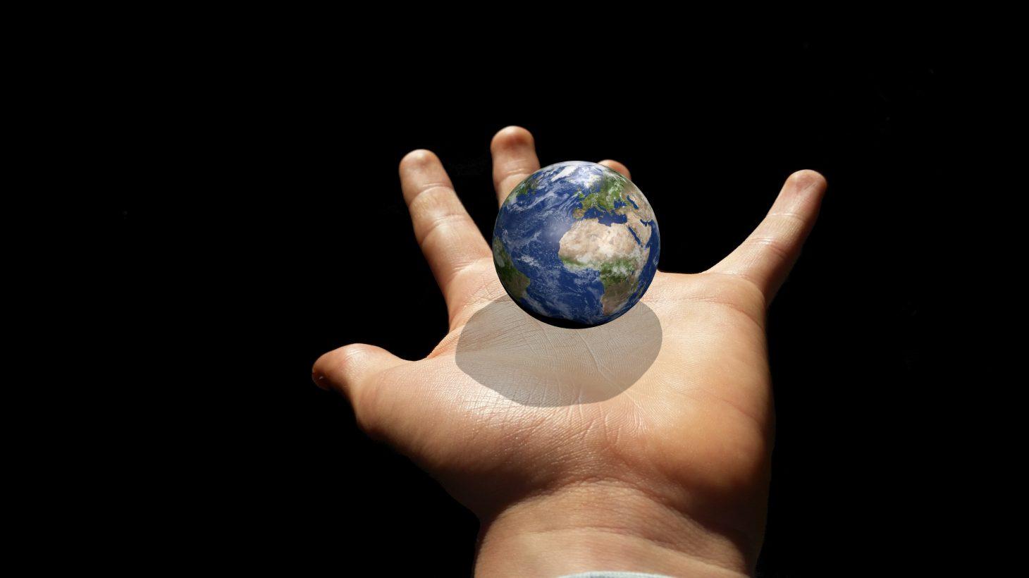 Ett litet jordklot som svävar ovanför en utsträckt handflata.