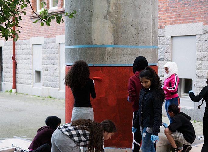 Elever målar en ventilationstrumma så den ser ut som en raket.