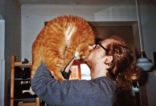 Fredrik Glückman, elevassistent på Sofielundsskolan lyfter upp och pussar katt.