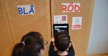 Förskollärare Anna Graca hjälper Emir läsa av en QR-kod.