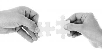 Händer håller varsin pusselbit som passar ihop.