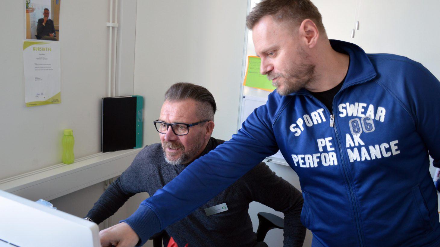 Magnus och Jörgen står framför dator och tittar på skärmen.