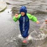 Barn springer i vattenpöl så det stänker.
