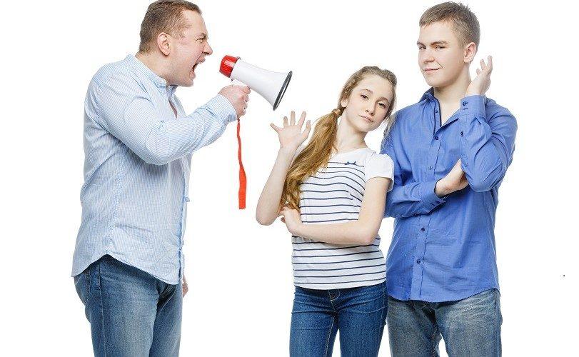 Man skriker i megafon på två barn som inte lyssnar.