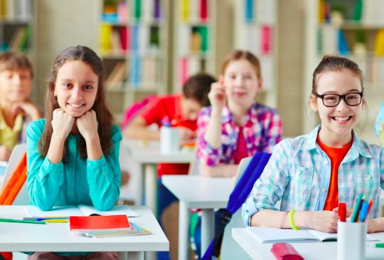 Elever sitter i skolbänkar och ler.