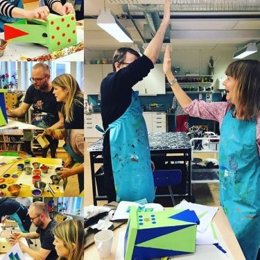 Lärare bygger fågelholkar och målar dem.