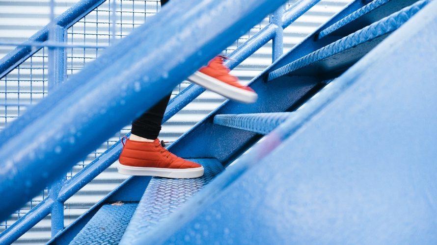 Fötter i röda skor går uppför trappa.