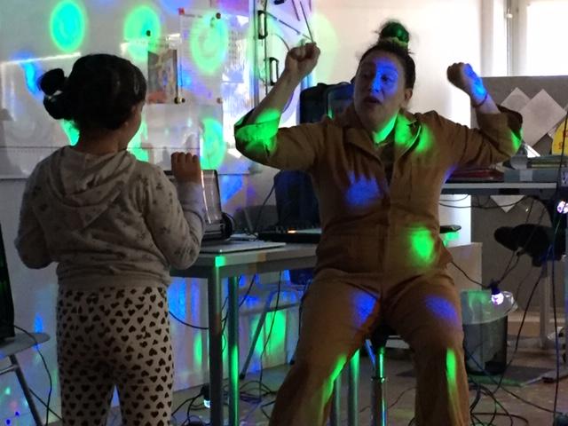 Kvinna och barn dansar i discoljus.