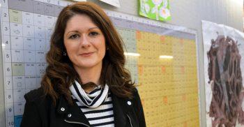 Amela Lagumdzija står framför en bliss-karta