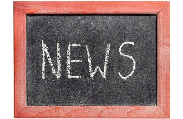 Texten news skriven på svart tavla med vit krita