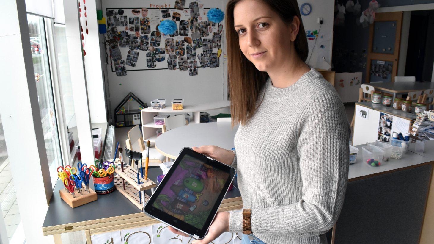 Isabel Schoszarzek, förskollärare på Pärlugglans förskola, håller upp ipad.