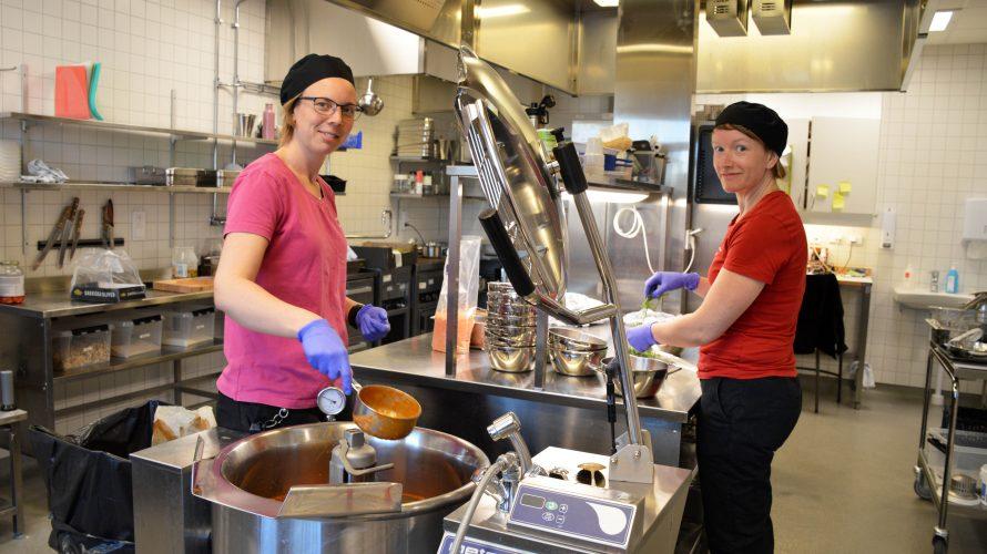 Två kvinnliga förskolekockar vid en stor gryta förbereder dagens lunchservering bestående av soppa.