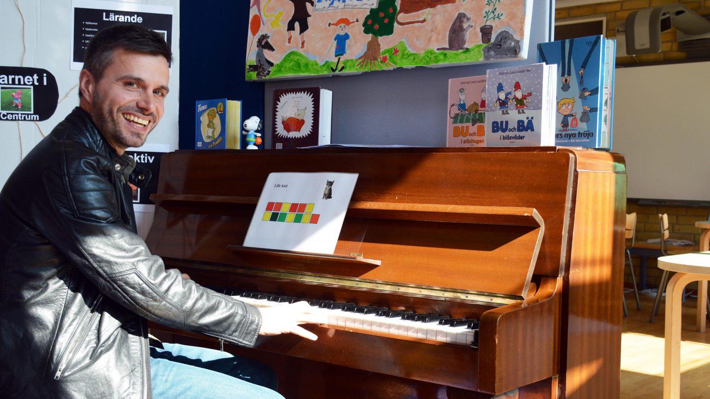 Gezim Isufi sitter framför ett piano.
