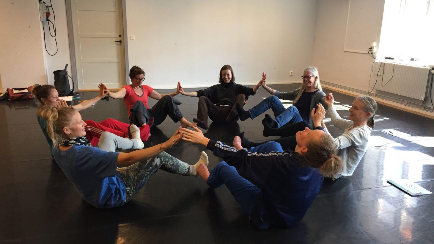 Pedagoger sitter i ring och sträcker ut händer och fötter.