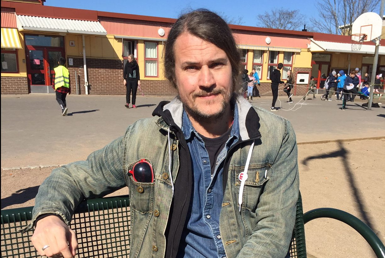 Oscar sitter på en bänk på Holmaskolans skolgård, i bakgrunden syns skolan och lekande barn