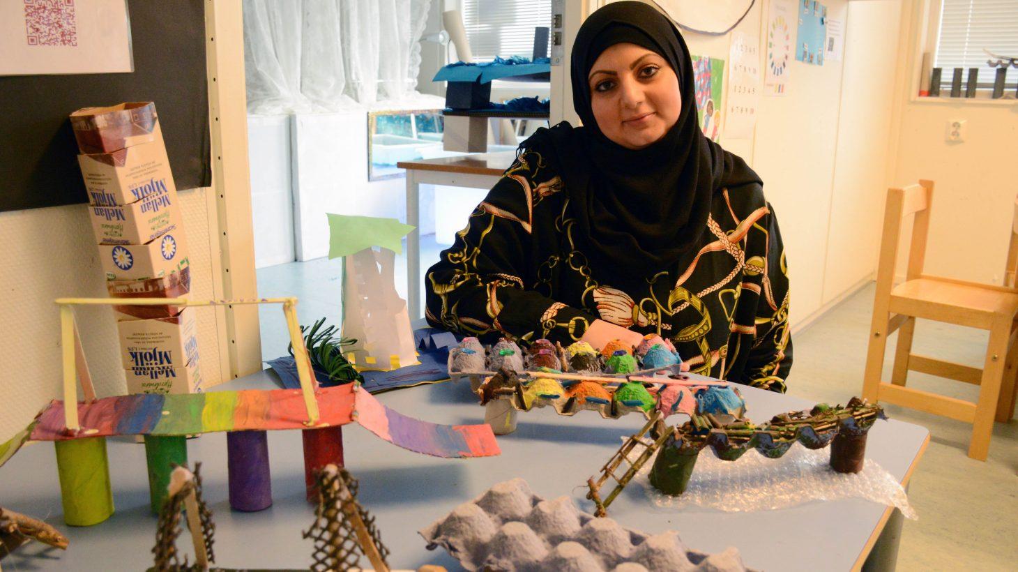 Barnskötare Sabah Baltaji vid ett bord med miniatyrer av Öresundsbron gjorda av återvinningsbart material.