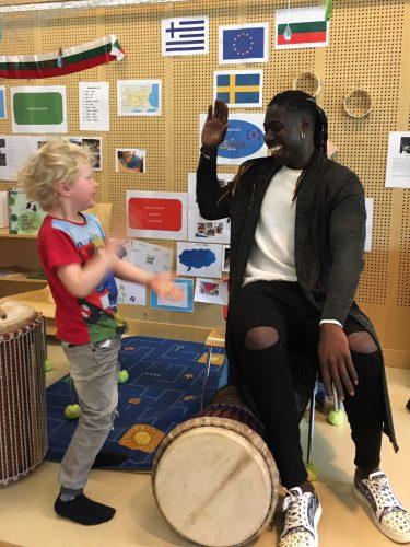 Man med trumma gör high five med dansande barn.
