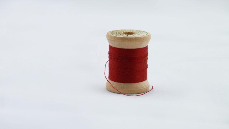 Trådrulle med röd tråd.
