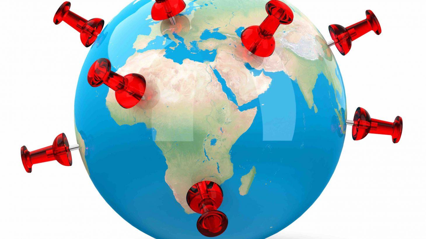En jordglob med röda häftstift som markerar platser runt om klotet.