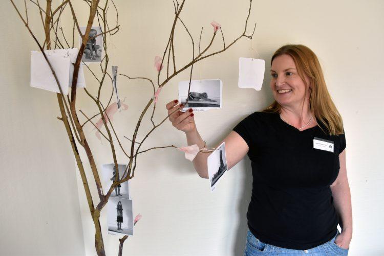 """Isabelle Åkerström, utvecklingspedagog i Pedagogiska utvecklingsteamet i område norr, vid ett """"yogaträd"""" med bilder från sagoyogan fastsatta i grenarna."""